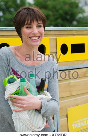 Femme portant des produits recyclables à centre de recyclage Banque D'Images