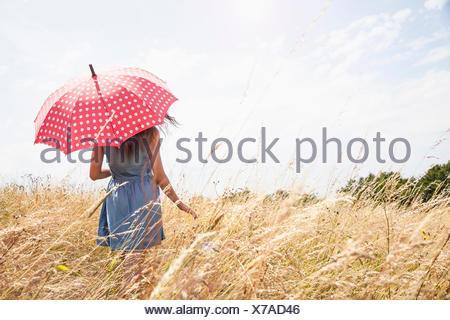 Jeune femme avec parapluie au champ Banque D'Images