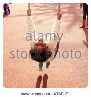 Portrait of a smiling girl sitting on a swing en aire de jeux Banque D'Images