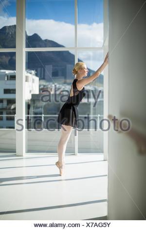 Ballerine s'étendant contre un mur dans le studio Banque D'Images