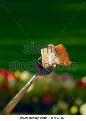 Close-up d'un morceau de hareng sur fourche contre les fleurs et l'herbe floue Banque D'Images