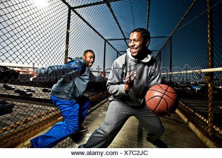 Deux amis jouer avec un terrain de basket-ball Banque D'Images