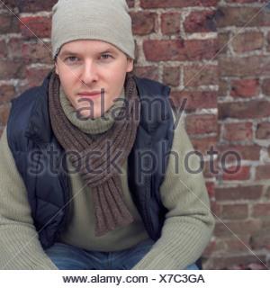 L'homme appuyé contre un mur de briques Banque D'Images