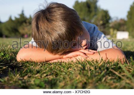 Garçon maussade, la tête en bas, couché sur l'herbe du parc Banque D'Images