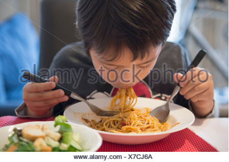 Boy eating spaghetti Banque D'Images