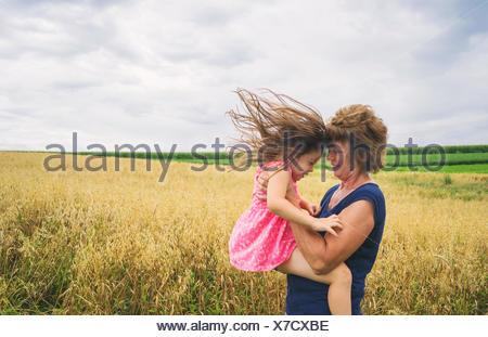 Les femmes mûres soulevant baby girl Banque D'Images
