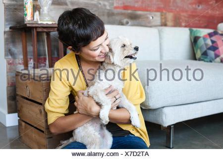Young woman hugging dog sur le plancher du salon Banque D'Images
