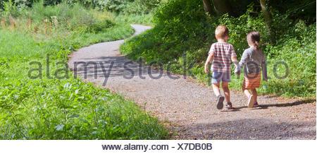 Fille et garçon marche main dans la main le long d'une route courbée, l'âge de trois ans Banque D'Images