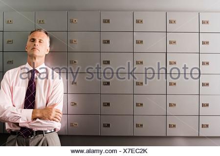 Businessman standing en face de la rangée de casiers bras croisés les yeux fermés en se penchant en arrière Banque D'Images