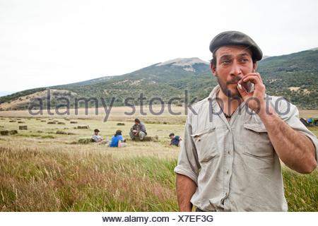 Un homme dans un béret avec une barbe fume une cigarette dans un pré de fauche avec quatre hommes en faisant une pause dans le foin fauché derrière lui. Banque D'Images
