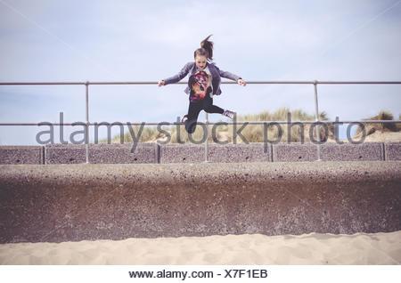 Fille sautant sur beach Banque D'Images
