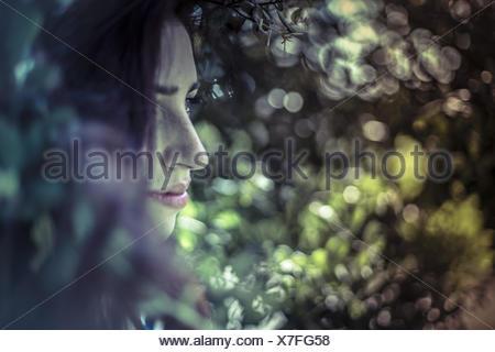 Mélancolie adolescente, jeune fille dans une forêt avec geste triste Banque D'Images
