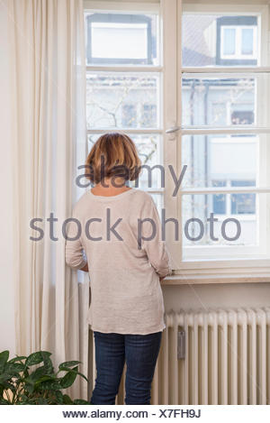 Vue arrière des hauts femme regardant à travers une fenêtre, Munich, Bavière, Allemagne Banque D'Images