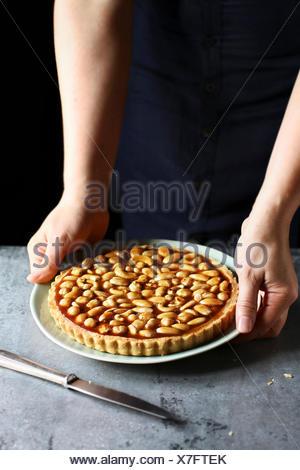 Les mains tenant un caramel tarte aux noix sur une plaque Banque D'Images