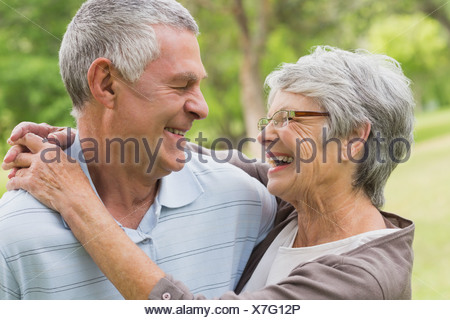 Happy senior woman embracing man at the park Banque D'Images