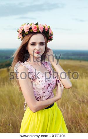 Belle fille à la mode très belle robe à fleurs sur le terrain. Belle fille avec gerbe de fleurs sur sa tête et bouquet de fleurs jaunes nombreuses sitting on meadow champ jaune en été. Banque D'Images