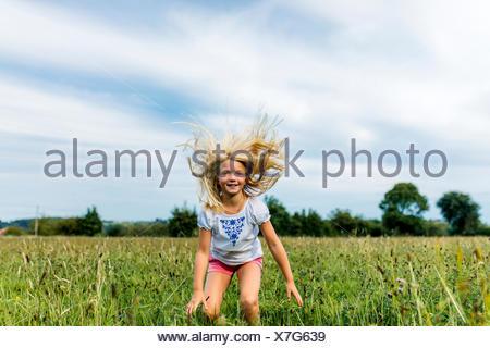 Portrait de jeune fille sautant en l'air sur un pré Banque D'Images