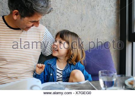 Girl rire avec père in cafe Banque D'Images