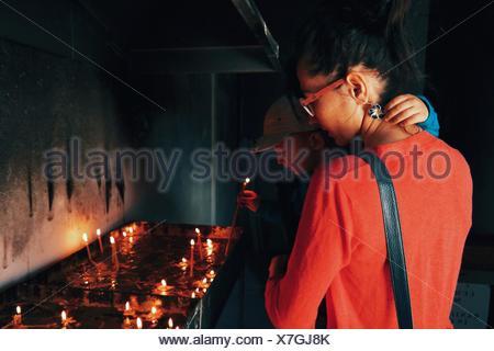 Son Holding bougie avec mère à l'Église Banque D'Images