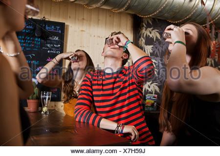 Jeunes amis de boire de verre en bar