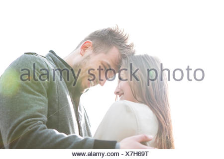 Smiling young man and woman embracing contre ciel clair Banque D'Images