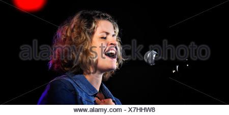 Vue panoramique sur une chanteuse singing into microphone sur un fond sombre Banque D'Images