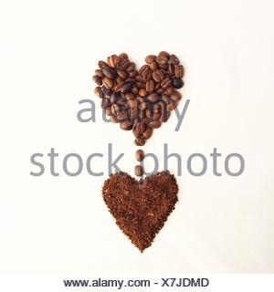 Café en grains en forme de coeur, des gouttes dans une autre forme de coeur de café Banque D'Images
