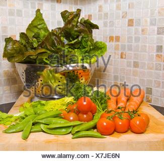 Des légumes frais et des fruits sur un bloc de coupe de bois dans la cuisine Banque D'Images