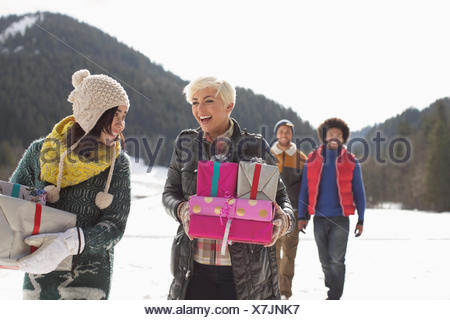 Les amis carrying Christmas gifts in snow Banque D'Images
