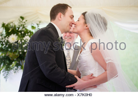 Newlywed couple kissing in wedding Banque D'Images