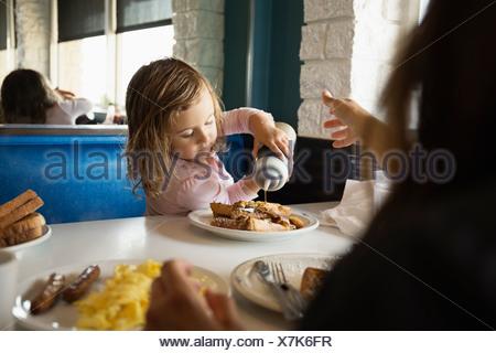Mère avec enfant fille pouring ketchup in diner Banque D'Images