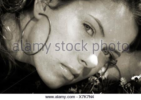 Laura, une jeune fille, portant sur l'herbe dans les marguerites. Banque D'Images