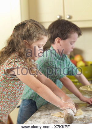 Cuisson enfants together in kitchen Banque D'Images