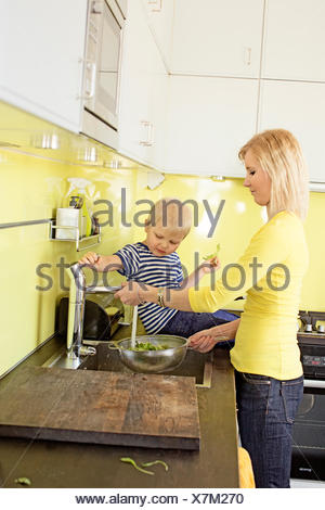 La Finlande, Helsinki, Kallio, Mère et fils en cuisine rincer la laitue dans une passoire Banque D'Images