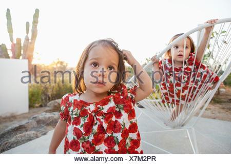 Lits bébé filles jouant sur patio Banque D'Images
