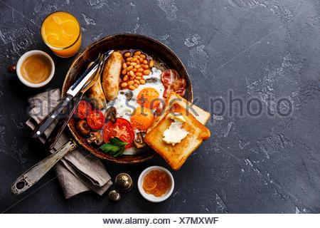 Petit-déjeuner anglais dans la casserole avec les œufs, saucisses, bacon, haricots, toasts et café sur pierre sombre contexte copy space Banque D'Images