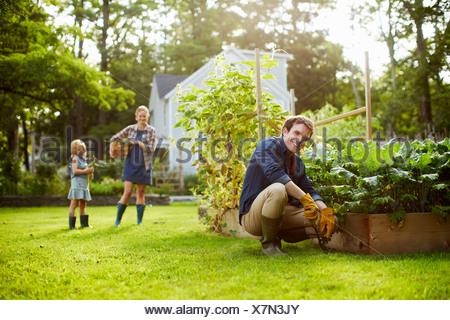 Trois personnes, deux adultes et un enfant dans un jardin potager. Banque D'Images