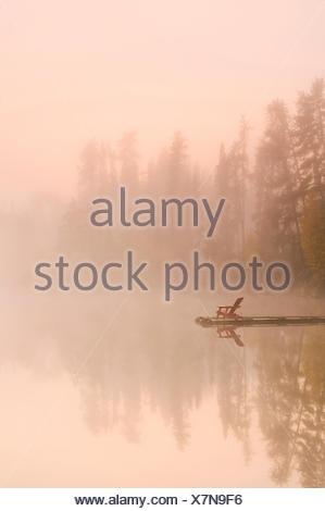 Fauteuil Muskoka sur dock, Dickens Lake, Nord de la Saskatchewan, Canada Banque D'Images