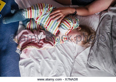 Portrait of woman touching baby girl on bed Banque D'Images