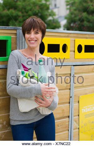Femme de prendre les produits recyclables à bac de recyclage Banque D'Images