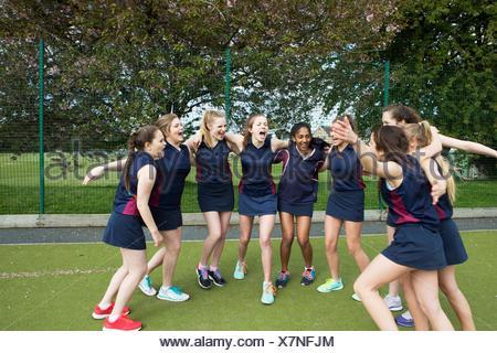 Groupe d'élèves de sexe féminin sur le terrain de sport, les bras autour de Banque D'Images