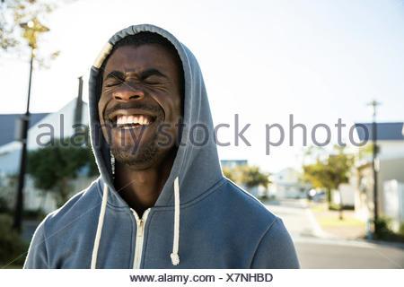Portrait of man wearing hooded top les yeux fermés riant Banque D'Images
