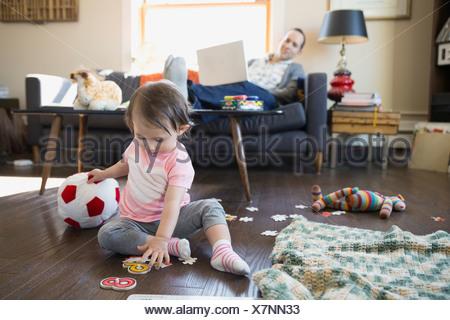 Père avec ordinateur portable en regardant sa petite fille jouer Banque D'Images