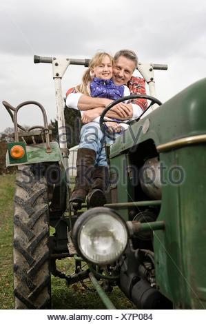 Farmer hugging daughter sur le tracteur Banque D'Images