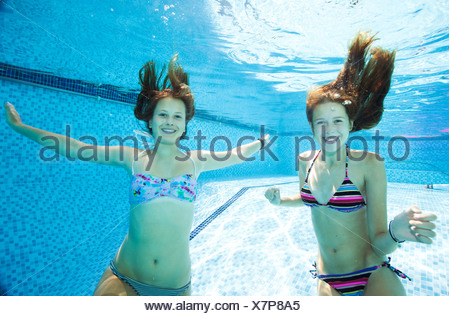 Deux adolescentes swimming underwater in swimming pool Banque D'Images
