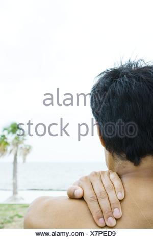 Homme à la plage, la main sur l'épaule, cropped vue arrière Banque D'Images