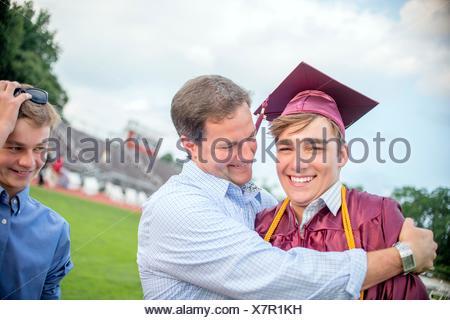 Jeune homme d'être embrassé par le père à la cérémonie de remise des diplômes