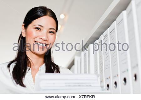 Businesswoman holding folder in library Banque D'Images