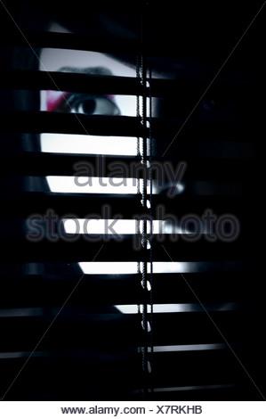 Un visage partiellement caché d'une jeune femme derrière un écran Banque D'Images
