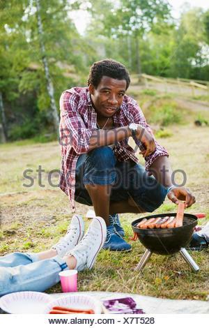 Portrait of smiling man grilling les saucisses sur le barbecue en forêt Banque D'Images